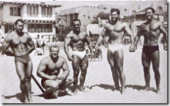 black and white pic of muscley men on a beach
